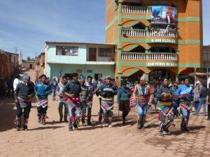 Villages arriving in Macha with music and dance.