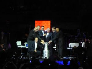 The seven Hall of Fame players from the team together with the cup.