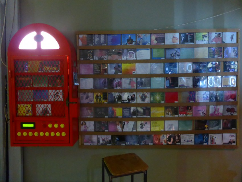 Jukebox and catalog on the wall next to it.