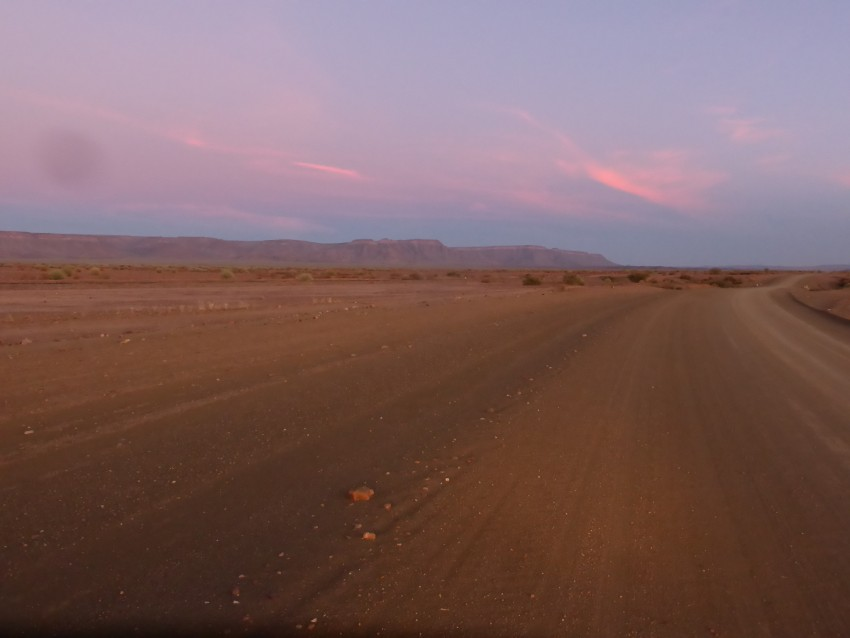 A determined man on the road to Fish River Canyon with beautiful pink sunset clouds on the horizon.